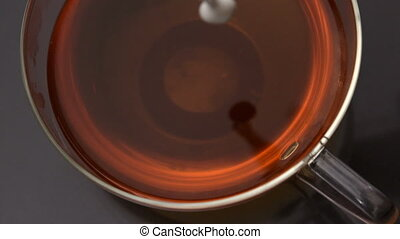 Milk pouring into cup of tea in slow motion