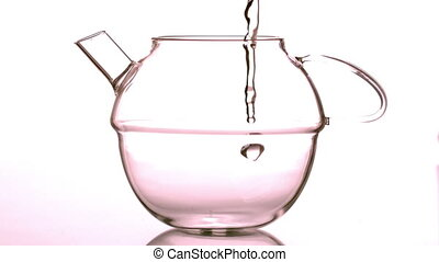 Water pouring into glass teapot