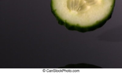 Courgette slice falling on wet black background in slow...