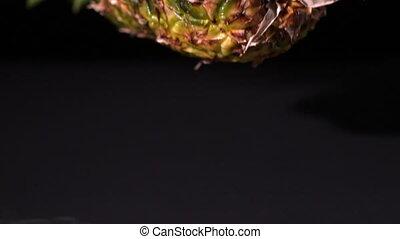 Pineapple falling and splitting on black background in slow...