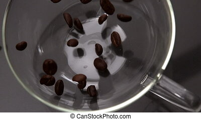 Coffee beans pouring into glass cup in slow motion