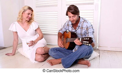 Romantic man playing guitar for his girlfriend at home in...