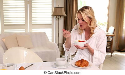 Woman in bathrobe eating breakfast at home in the living...