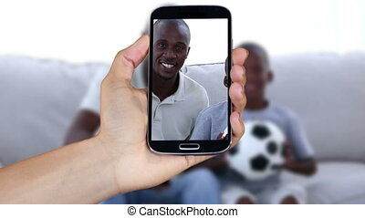 Hand showing people watching football clips on smartphone...