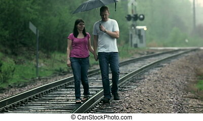 Walking in the rain - Young couple man and woman, playfully...