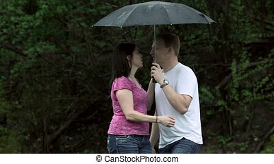 Kissing under an umbrella - Young couple man and woman,...