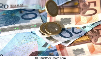 Euro coins dropping onto notes in slow motion