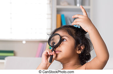 Indian girl peeking through magnifying glass.
