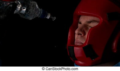 Boxer pouring water from bottle over face in slow motion
