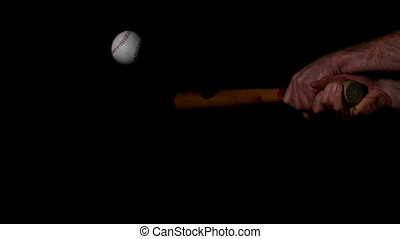 Man hitting baseball with bat on black background in slow...
