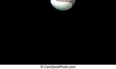 Baseball falling in water on black background in slow motion
