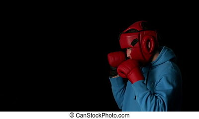 Sporty young man boxing on black background in slow motion