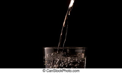 Water pouring into glass on black background in slow motion