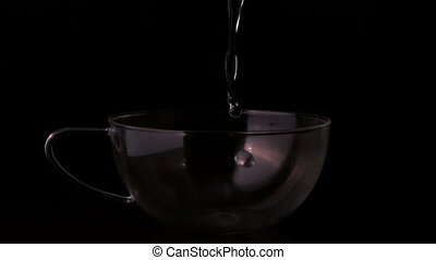 Water pouring into clear cup