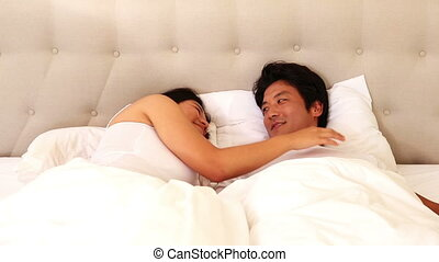Loving asian couple lying in bed together at home in bedroom