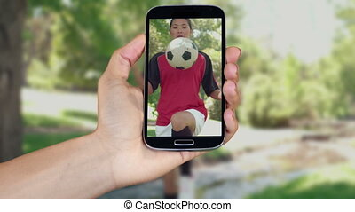 Hand showing girls playing football clips on smartphone...