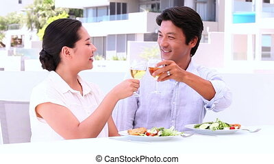 Asian couple having white wine with meal
