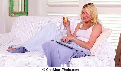 Pretty blonde relaxing on sofa with tablet and wine - Pretty...