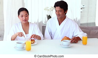 Asian couple having breakfast together at home in the living...