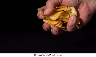 Hands crushing potato chips on black background in slow...