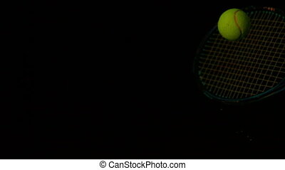 Tennis racket hitting a ball on black background in slow...