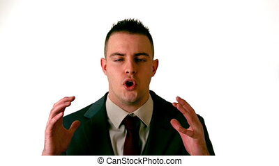Businessman shouting at the camera on white background in...