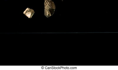 Gold nuggets falling into water - Gold nuggets falling into...