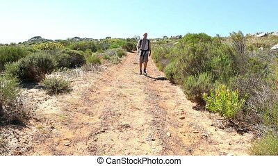 Man hiking in nature on wild trail on a sunny day
