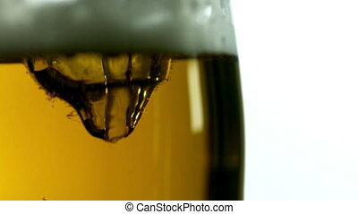 Glass of beer bubbling on white background in slow motion