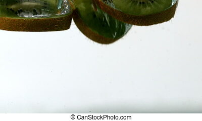 Kiwi slices falling into water in slow motion
