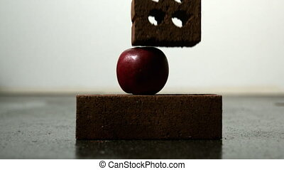Apple being squashed between two bricks in slow motion