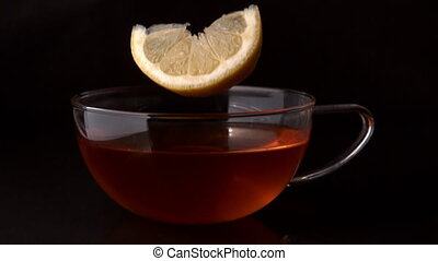 Lemon slice falling in cup of tea in slow motion