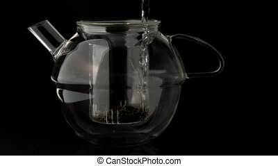 Water pouring into glass teapot ov