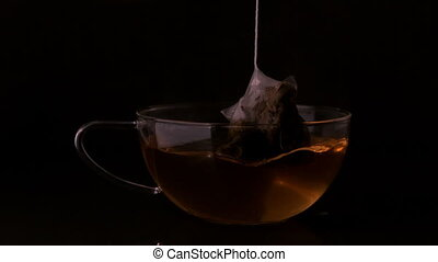 Teabag dunking into glass cup in slow motion