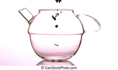 Loose herbal tea falling into glass teapot in slow motion