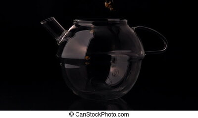 Herbal tea pouring into glass teapot in slow motion