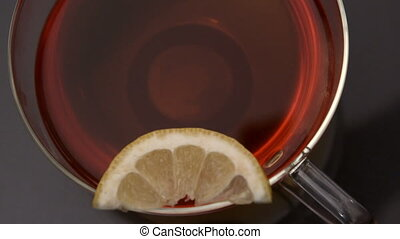 Lemon slice falling in cup of tea