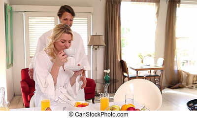 Couple in bathrobes spending the morning together at home in...