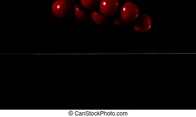 Cherry tomatoes falling in water on