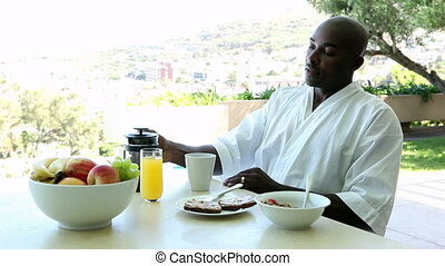 Man eating breakfast outside on a sunny day