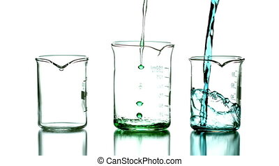 Liquid pouring into beakers on white background in slow...