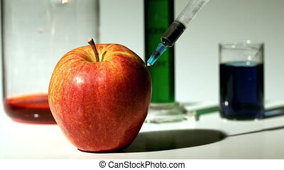 Syringe injecting chemical into an apple in slow motion