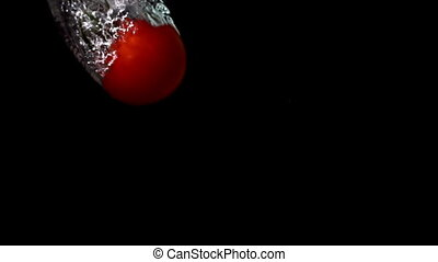 Tomato falling in water on black background in slow motion