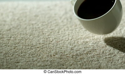 Cup of coffee falling and spilling over carpet in slow...