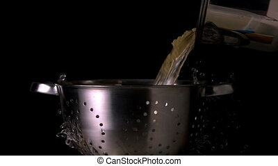 Pot pouring pasta and water through colander in slow motion...