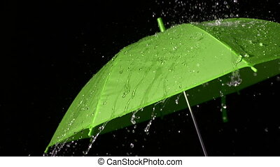 Rain falling on green umbrella in slow motion