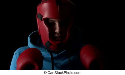 Sporty young man boxing on black