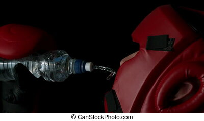 Boxer pouring water from bottle into mouth in slow motion