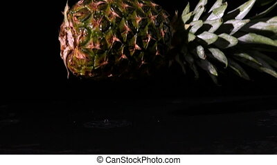 Pineapple falling on wet black surface in slow motion