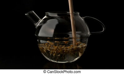 Wooden stick stirring teapot of water and loose tea in slow...